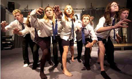 Teenagers in school uniforms in a drama class