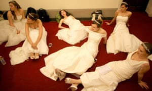 Debutantes rest their feet as they await the arrival of guests during the Queen Charlotte's Ball at the Royal Courts of Justice in London.