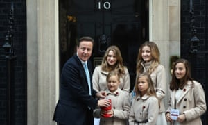 David Cameron makes a donation before being presented with a poppy by members of a group called 'The Poppy Girls' at 10 Downing Street. The Poppy Girls will be releasing The Royal British Legion's annual single on Remembrance Sunday.