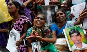 Tamil women hold images of their disappeared relatives