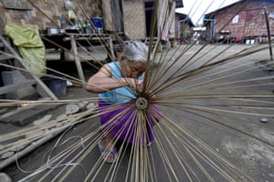An elderly Kachin refugee woman maiking a broom at the Janmai Baptist camp, Myitkyina, Kachin State. Since 2011, thousands of local people left their homes and took shelter in refugee camps to escape the ongoing battles between the Myanmar government's troops and the Kachin Independence Army (KIA).