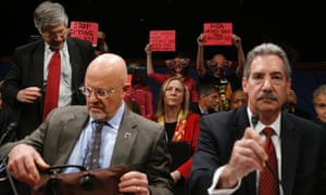 U.S. Director of National Intelligence James Clapper (seated, L) and Deputy Attorney General James Cole prepare to testify at a House Intelligence Committee hearing as protesters hold up signs in the audience on Capitol Hill in Washington. The hearing was on the potential changes to the foreign intellience surveillance act (FISA).