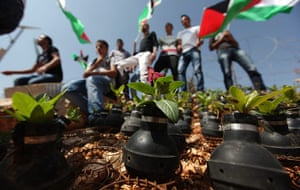 tear gas garden: Palestinian activists stand near roses planted in used tear gas canisters