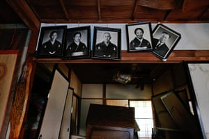 Fukushima: Portraits hang from the wall of an abandoned and damaged house