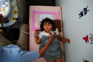 Fukushima: A doctor conducts a thyroid examination on four year old Maria Sakamoto