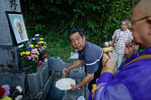 Fukushima: A relative of Yotsuno Kanno puts her remains into a family grave