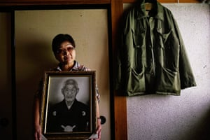 Fukushima: Mieko Okubo, 59, poses with a portrait of her father-in-law Fumio Okubo