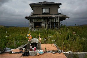 Fukushima: A small monument to victims is seen in front of an abandoned house in Namie