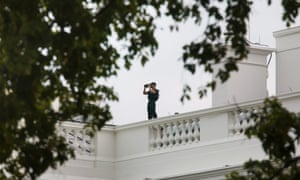 A Secret Service agent stands on top of the White House after a person allegedly tried to ram their car through gates to the White House,