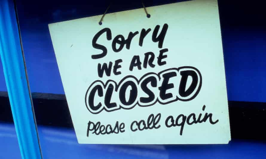 Detail of a shop door with sign stating Sorry We Are Closed Please Call Again.