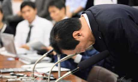 Mizuho Financial Group chairman Yasuhiro Sato bows in apology