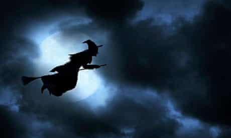A Halloween witch flies across the face of the moon