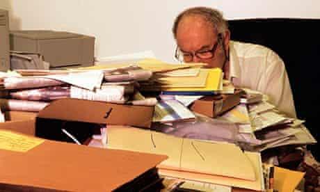 man behind messy desk