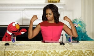 First lady Michelle Obama, flexes her arms for PBS Sesame Street's characters Elmo, left, and Rosita, right, during an event to help promote fresh fruit and vegetable consumption in the State Dining Room of the White House.