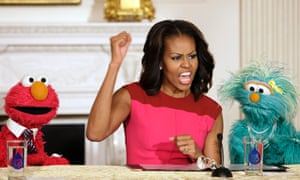 Michelle Obama reacts between PBS Sesame Street characters Elmo and Rosita after delivering remarks on marketing healthier foods to children at the White House in Washington.