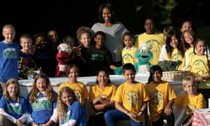 Michelle Obama  poses for a photo with school children and Sesame Street's Elmo and Rosalita after harvesting fruits and vegetables from the White House kitchen garden.