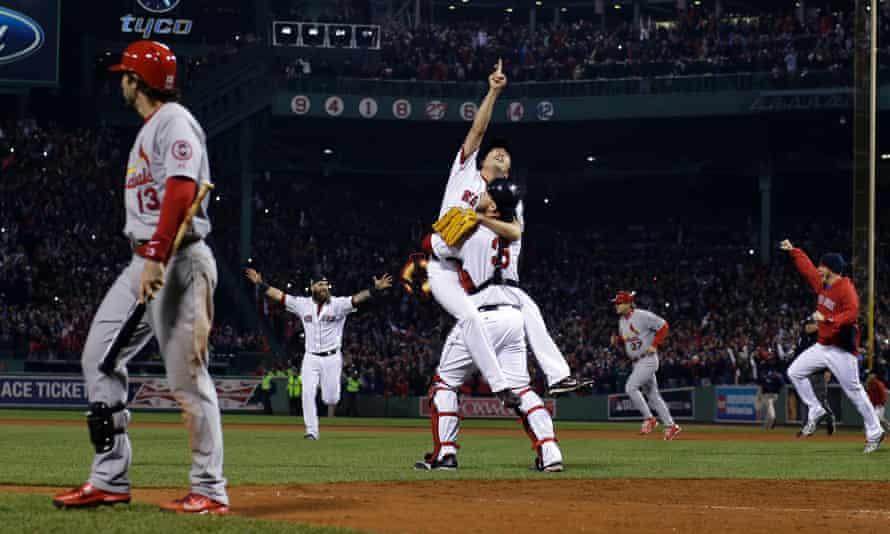 A study of contrasts: Pitcher Koji Uehara and catcher David Ross of the Boston Red Sox celebrate winning the 2013 World Series as Matt Carpenter of the St Louis Cardinals walks off the field.