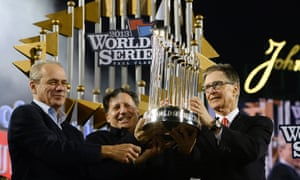 Boston Red Sox President Larry Lucchino, Chairman Tom Werner and owner John Henry hoist the Commissioner's Trophy