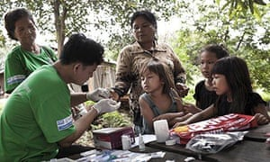 A village health worker tests a woman for malaria in Pailin as part of Malaria Consortium's Malaria