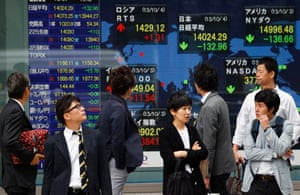 Passers-by watch an electronic stock board of a securities firm in Tokyo, Friday, Oct. 4, 2013.