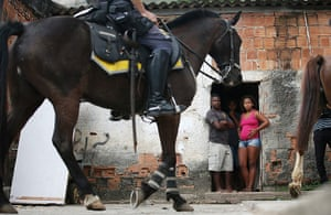 Favela clearance: Residents watch police as they patrol on horseback patrol during a pacifica