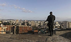 A police officer stands guard during a pacification operation in the Lins favela complex in Rio