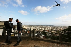 Favela clearance: Special forces soldiers stand by as a military helicopter flies overhead  d