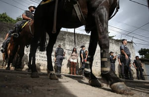 Favela clearances: Residents watch as military police on horseback patrol during a 'pacificati