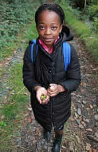 A child holding some acorns