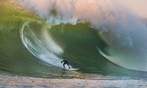 Surfer riding Mavericks, at Monterey Bay, California.