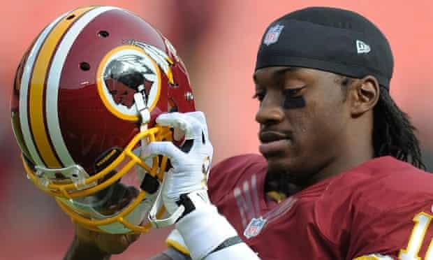 Washington Redskins quarterback Robert Griffin III prepares to put on his helmet.