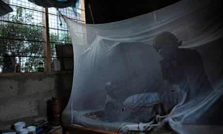 A mother and her child sit on a bed covered with a mosquito net in Bagamoyo, Tanzania