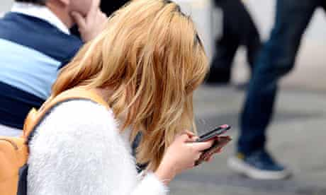 A young woman looks at her mobile phone in Brisbane