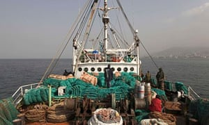 Sierra Leonean security forces supervise crew of a vessel caught for alleged illegal fishing in 2012