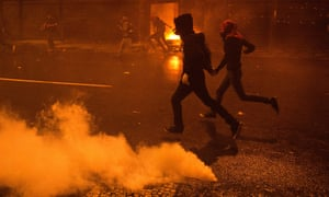 Masked demonstrators run for cover during clashes with police at the end of a teachers' protest demanding better working conditions in Rio de Janeiro, Brtazil.