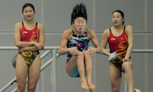 Hair-raising: A Japanese diver practices beside two Chinese divers before competing in the Women's synchronized 3m springboard final at the East Asian Games held at the Tianjin Olympic Centre, China.