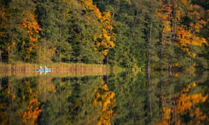A perfect autumnal scenes on Lake Treplin, Germany, as two anglers head out for some early morning fishing.