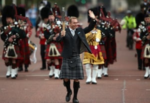 Sir Chris Hoy MBE walks up the Mall holding the Commonwealth Games baton as he heads towards Buckingham Palace in London, England. After presenting the baton to Queen Elizabeth II, the relay will continue it's journey visiting all 70 competing nations and territories ahead of the Commonwealth Games in Glasgow in 2014.