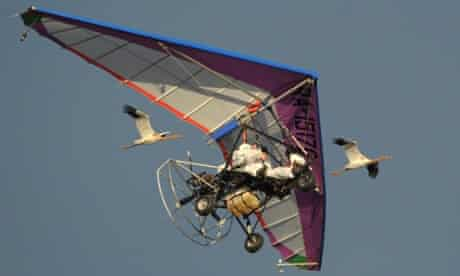 Vladimir Putin flies in the sky with a motorized hand glider as young cranes follow him in  the Kushevat ornithological nature reserve.
