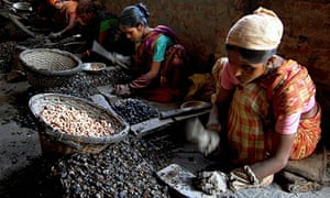 Indian women work at a cashew factory in Agartala