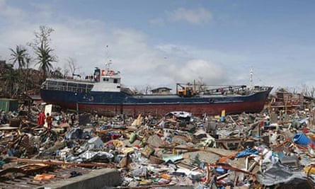 A boat washed ashore sits on destroyed houses in Tacloban.