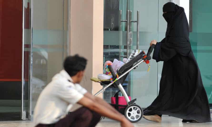 A Saudi woman walks past a foreign worker at a shopping mall.