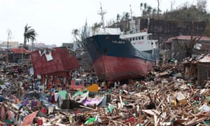 Survivors walk past a ship that lies on top of damaged homes after it was washed ashore in Tacloban city, Leyte province central Philippines on Sunday, Nov. 10, 2013.