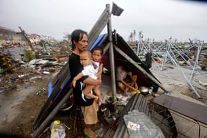 Typhoon hits Tacloban: a father waits with his children for food relief