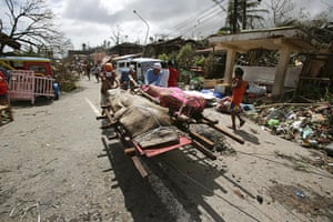 Typhoon hits Tacloban: residents push dead bodies on a cart