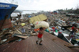 Typhoon hits Tacloban: residents carry relief goods