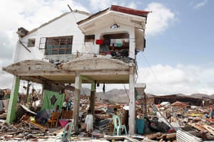 Typhoon hits Tacloban: survivors stand in their damaged house in Tacloban