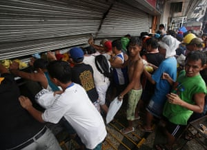 Typhoon hits Tacloban: residents push open a shutter on a small grocery shop to get food in Taclob