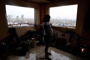 Typhoon hits Tacloban: a pregnant woman cooks a meal inside a building overlooking devastation