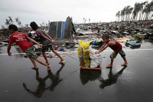Typhoon hits Tacloban: residents carry relief goods past damaged homes